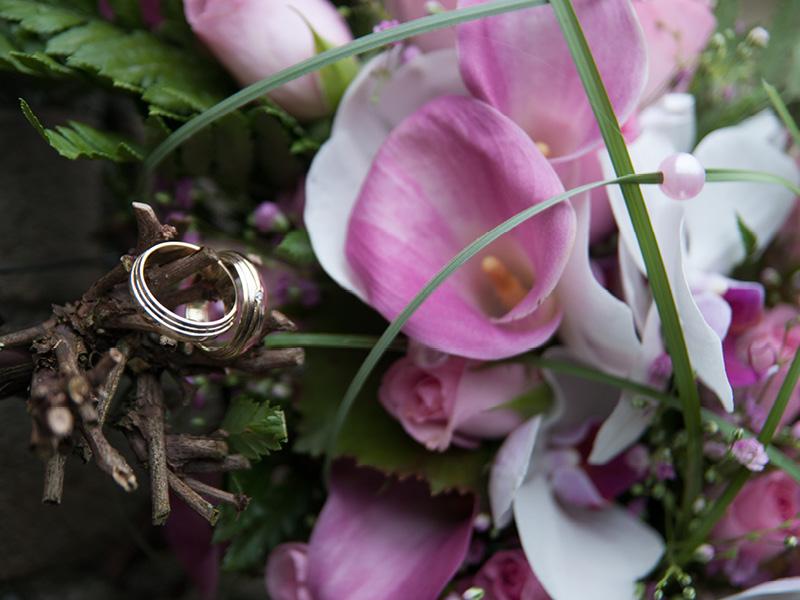 close-up van het bruidsboeket en de trouwringen